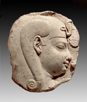 The relief sculpture of a Child-god is a particularly fine example of a 'sculptor's model' or 'votive object,' a piece appearing to be a fragment but actually a fully realized object in itself. It is probably Harpokrates, Horus the Child, often found in 'birthing' temples, or in artisans workshops associated with the temples, of the Ptolemaic period. Harpokrates is often portrayed sucking his finger, possibly seen here in unfinished form to the right of his mouth. Also common to Harpokrates is the child's side-lock which curls elegantly down the side of his head. The curling lock is echoed in the smaller curl of the uraeus (upright cobra) on his skullcap, which signifies divine sovereignty. The full cheeks and neck creases suggest a very young child, also common to portrayals of Harpokrates. The carving demonstrates assurance in the delicate quality of the beautifully shaped eyes and mouth, the lovely fullness of the eyebrow and the slight, beneficent smile.<br /><br />